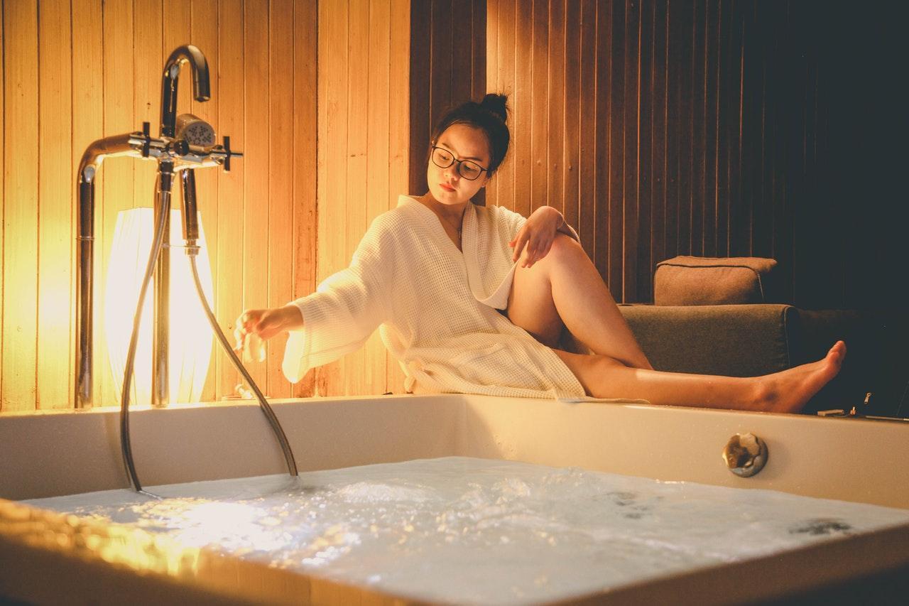 Frau sitzt an einer Badewanne mit Whirlpool